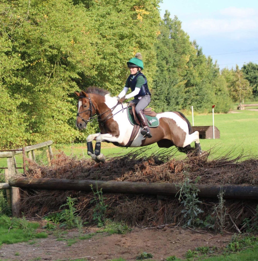 Maisie Randle and horse jumping cross country fence